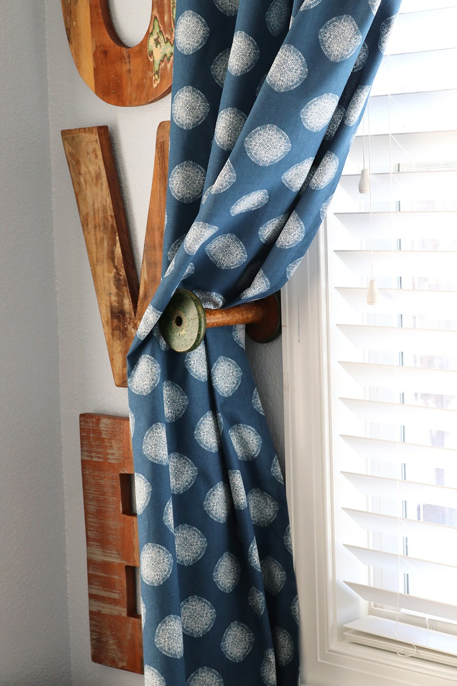 use a vintage thread spool as a curtain tie back!